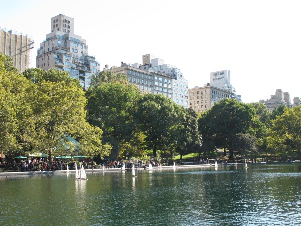 People sit on the benches lining Conservation Water, with the apartments of 5th Ave towering above.