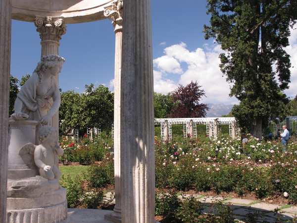 Statue near the rose garden, with mountains in the background.
