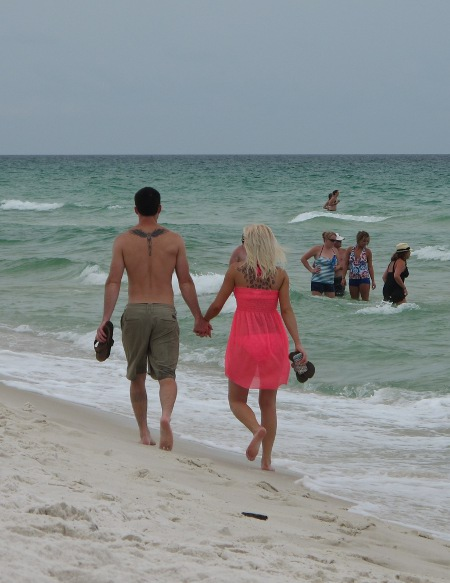 A couple strolls along the shore during the summer season.
