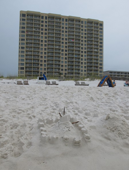 Sandcastle on the shore and highrise in the distance.