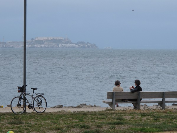 Women chat on a bench by the water.