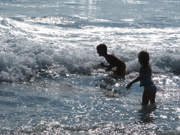 Kids playing in the waves at high tide.