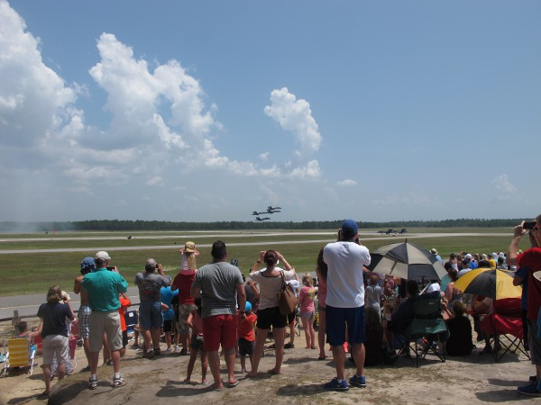 The crowd watching four planes fly low.