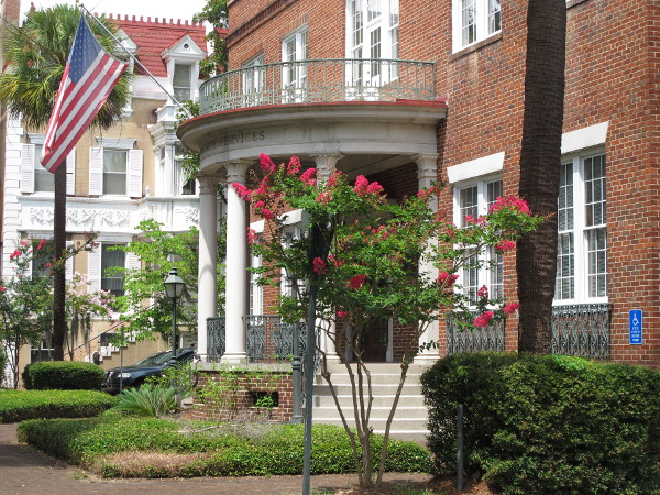 Brick building with columns and American flag at Monterey Square.