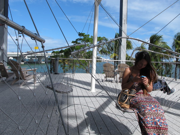 A girl checks her phone while sitting on a swing.