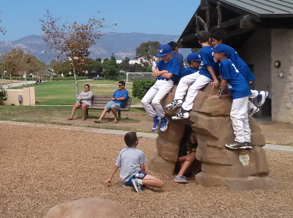 Baseball boys enjoying the rock arch on the playground.