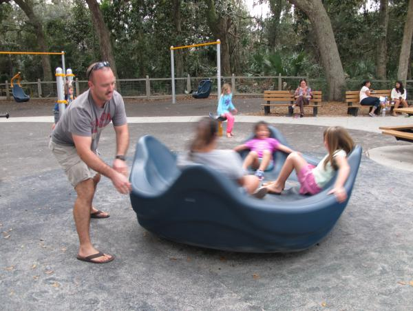 A dad pushes kids on the spinner.