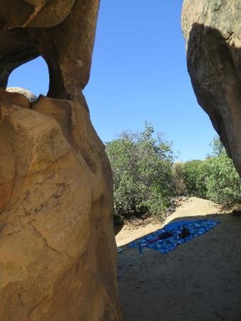 Picnic blanket in the shade of boulders.