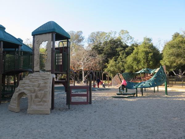 Play structure for big kids, sandy floor, climby, and swings.