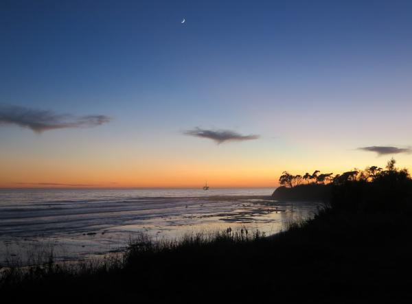 Moon and curve of beach, at nightfall.
