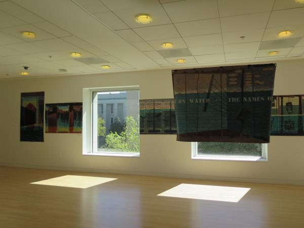 Exhibit in a hallway with square windows.