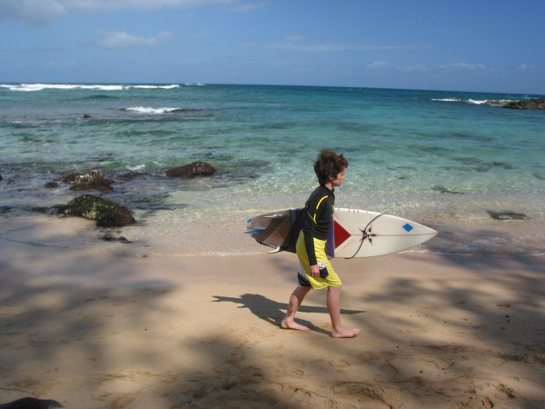 A young surfer arrives to check out the waves. Laniakea Beach was just a surfing beach before the turtles made it their home.