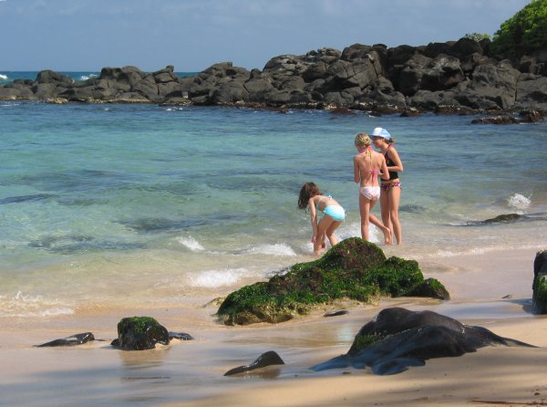 Three girls play by the shore at Turtle Beach.