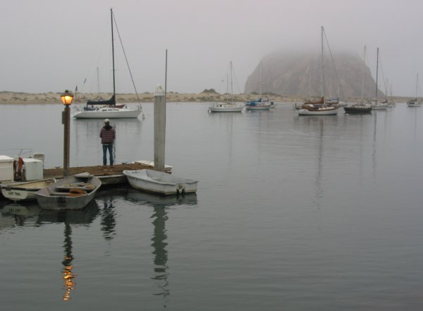 A fisherman on the dock in the morning. Morro Rock stands in the distance.