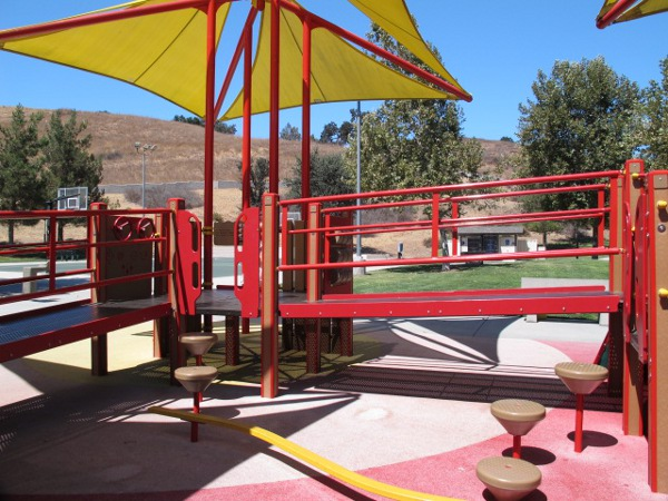 The playground is pretty with its bright yellow canopies and hills behind.