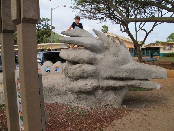 A boy climbs the sea monster.