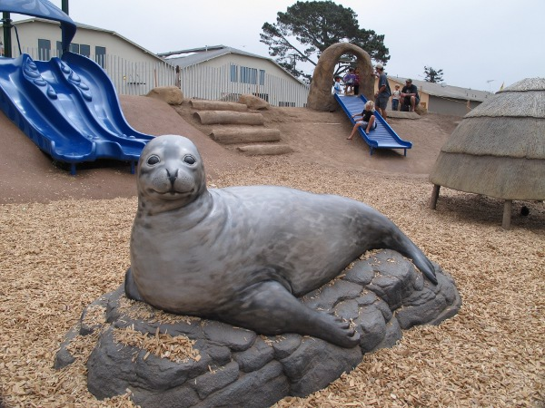 Cute seal sculpture with slides behind.