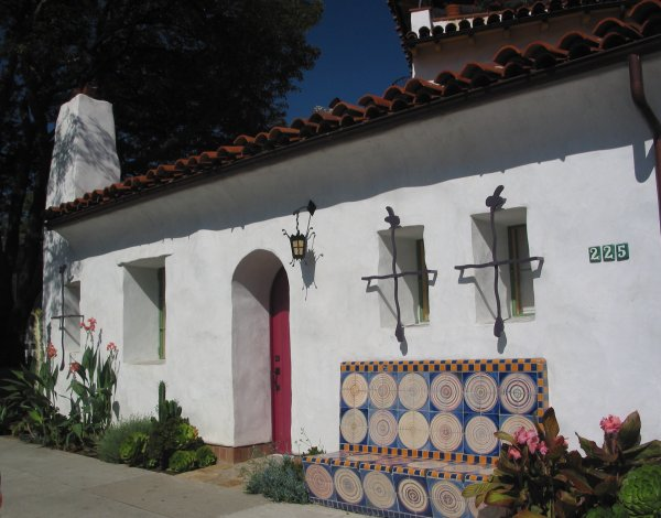 Notice the ironwork lantern and window grills. Notice the red door, the ceramic bench, and the rose cactus.
