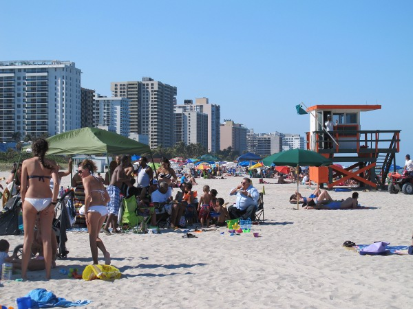 Crowds of people on the soft sand, with high rises in the distance.